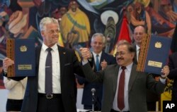 FILE - ACI Systems GmbH's President Wolfgang Schmutz from Germany, left, and manager of state company of Yacimientos Boliviano de Litio, Juan Carlos Montenegro, pose for photos during a signing ceremony in government palace in La Paz, Bolivia, Oct. 5, 2018.