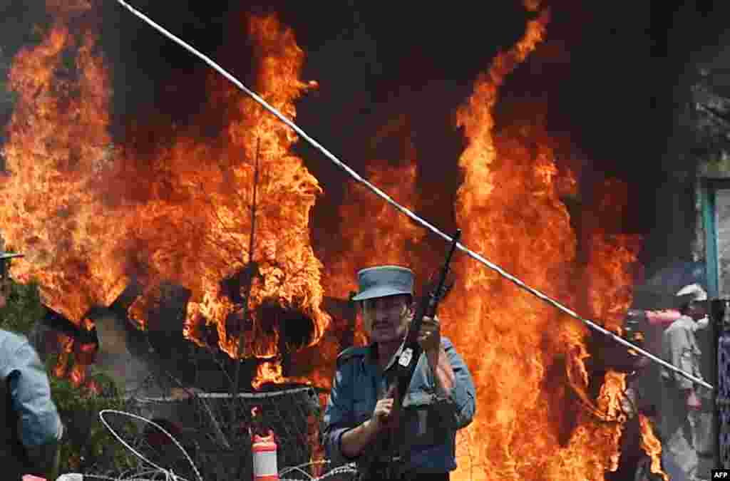 An Afghan policeman stands guard as smoke and flames rise from the site of a huge blast near the entrance of Kabul's international airport.