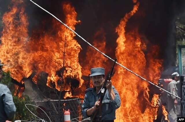 FILE - An Afghan policeman stands guard as smoke and flames rise from the site of a huge blast struck near the entrance of Kabul's international airport, in Kabul on August 10, 2015.