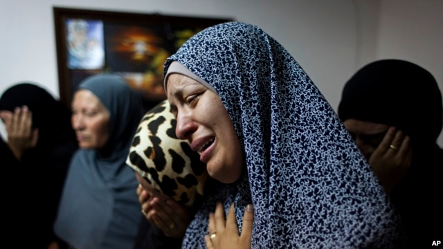 Female relatives of slain Palestinian Ahmad Arafat Sabarin, 20, who was killed by Israeli army fire early Monday during a confrontation between stone throwers and Israeli soldiers, cries with a relative at the family house, prior to his funeral procession in the refugee camp of Jalazoun, on the outskirts of Ramallah, Monday, June 16, 2014.
