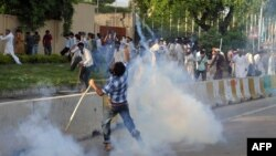 A Pakistani Muslim protester throws a tear gas shell back towards police as demonstrators attempt to reach the U.S. embassy during a protest against an anti-Islam film in Islamabad, September 20, 2012.