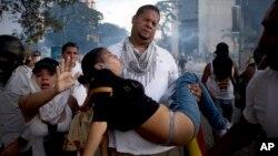 Un hombre carga a una mujer afectada por los gases lacrimógenos disparados por los policías antimotines en una protesta en Caracas, el sábado 22.