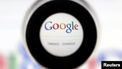 FILE - A Google search page is seen through a magnifying glass in this photo illustration.