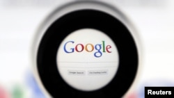 FILE - A Google search page is seen through a magnifying glass in this photo illustration taken in Brussels.