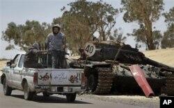 Des rebelles libyens passant près d'un tank gouvernemental détruit par l'OTAN