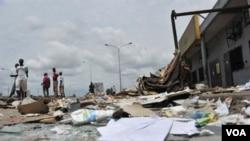 Warga berjalan melewati daerah yang hancur dijarah di distrik Abobo di Abidjan, Rabu (2/3).