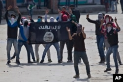 Kashmiri Muslim protesters hold a flag of Islamic State as they shout anti-India slogans during a protest in Srinagar, Indian controlled Kashmir, April 8, 2016.