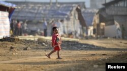A refugee child from Burma's Bhamo city walks inside a rescue camp in the Chinese southwestern border city of Longchuan, Yunnan province February 10, 2012. In an obscure part of southwest China, a refugee crisis from one of the world's longest running and