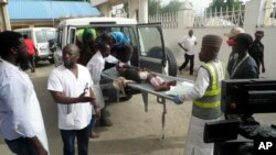 Des agents de la santé embarquent une personne blessée dans une ambulance à la suite d'un attentat-suicide à Damboa, Borno (Nigeria), le 17 juin 2018.