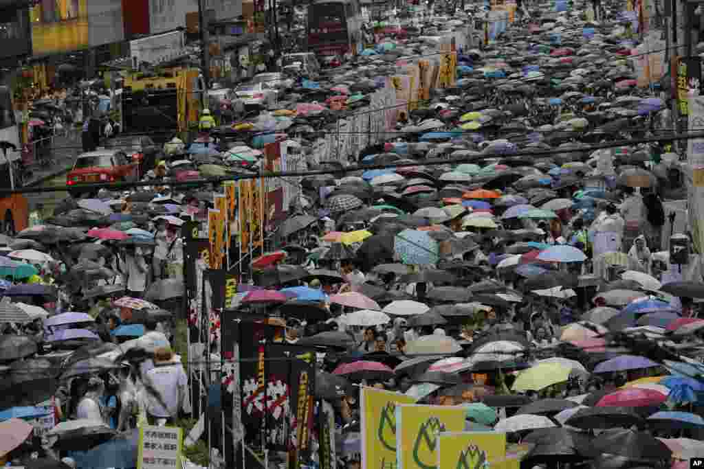 Hong Kong residents march through the streets of the former British colony carrying umbrellas during a protest to push for greater democracy, Hong Kong, July 1, 2014.