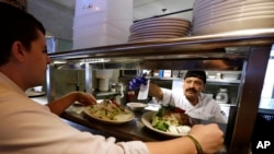 FILE - Cook Bulmaro Sosa, right, goes over a food order with server Zachary DeYoung at an Ivar's restaurant in Seattle.