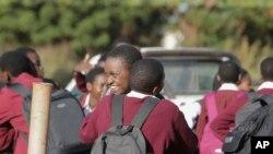 Des écoliers s'embrassent le dernier jour d'école à Harare, au Zimbabwe, le mardi 24 mars 2020. (AP Photo/Tsvangirayi Mukwazhi)