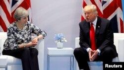 La primera ministra británicia, Theresa May, conversa con el presidente estadounidense, Donald Trump, durante la cumbre del G-20 en Hamburgo, Alemania, el 8 de julio de 2017.