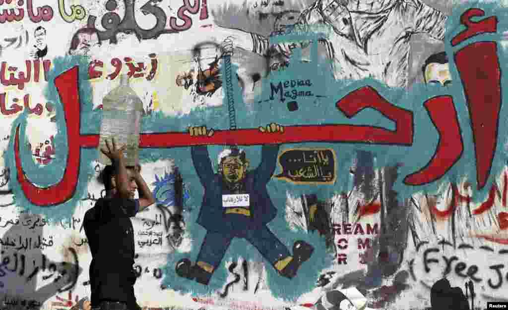 """Un hombre transportando un contenedor de agua sobre su cabeza pasa frente a un muro cubierto de graffitis en oposición al depuesto ex presidente Mohamed Morsi con el mensaje """"Fuera"""", en la plaza Tahrir (Liberación), de El Cairo."""