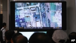 FILE - South Koreans watch a television broadcasting a satellite image of the nuclear facility in North Korea, at the Seoul Railway Station in Seoul, South Korea.
