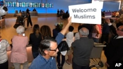 John Wider holds up a sign welcoming Muslims in the Tom Bradley International Terminal at Los Angeles International Airport, June 29, 2017.