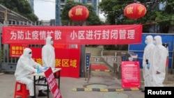 身穿防護服的工作人員在武漢一個住宅小區的入口設立登記與體溫測量的檢查點。 (2020年2月13日)