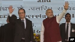 French President Francois Hollande, left, and Indian Prime Minister Narendra Modi wave at the audience as they arrive for the foundation stone laying for the headquarters of the International Solar Allliance at Gurgaon, outskirts of New Delhi, Jan. 25, 2016.