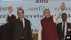 French President Francois Hollande, left, and Indian Prime Minister Narendra Modi wave at the audience as they arrive for the foundation stone laying for the headquarters of the International Solar Allliance at Gurgaon, outskirts of New Delhi, India, Jan.