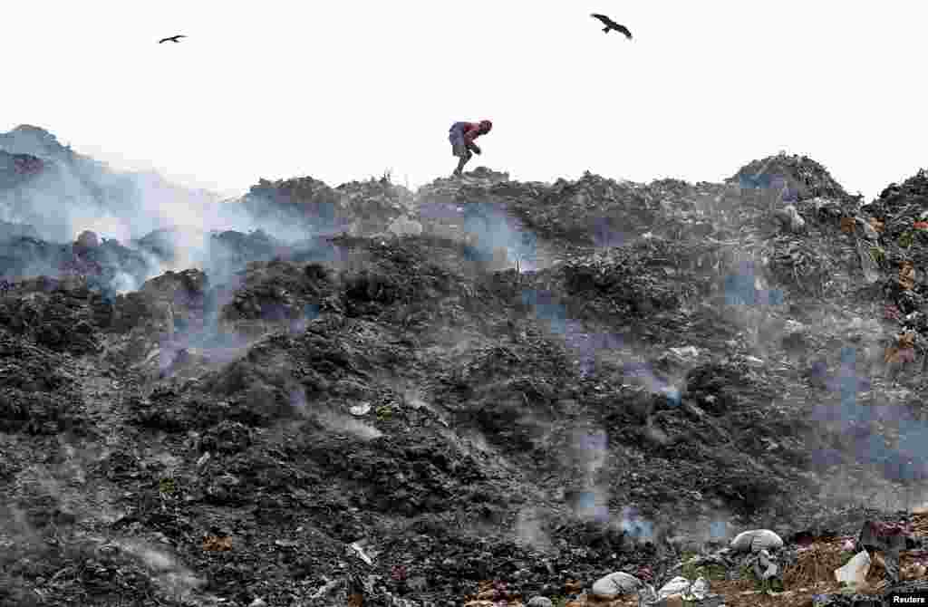 A man collects recyclable materials as smoke billows from a burning garbage dump site in Kolkata, India.