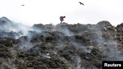 A man collects recyclable materials as smoke billows from a burning garbage dump site on the occasion of Earth Day, in Kolkata, India, April 22, 2018.