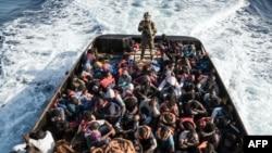 Un garde-côte libyen surveille 147 immigrants clandestins qui essayaient d'atteindre l'Europe au large de la ville côtière de Zawiyah, à 45 kilomètres à l'ouest de la capitale Tripoli, le 27 juin 2017.