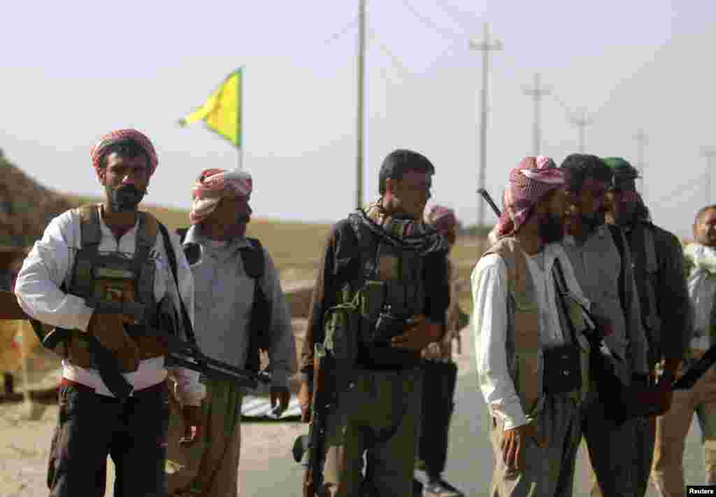 Yazidi fighters who recently joined the Kurdish People's Protection Units (YPG) secure a road in Mount Sinjar in northern Iraq, Aug. 13, 2014.