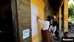 An election worker posts a voter list outside a polling booth at a school in Phnom Penh, Cambodia, July 28, 2018. The main opposition party was banned in November.