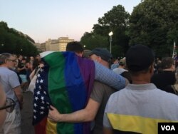 Many partners at the vigil hugged, wrapping the rainbow flags of gay pride around each other. (K. Gypson/VOA)