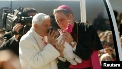 Paus Benediktus memberkati seorang bayi saat mengelilingi lapangan Santo Peter dengan kendaraan dalam pertemuan terakhir di hadapan publik Vatikan (27/2).