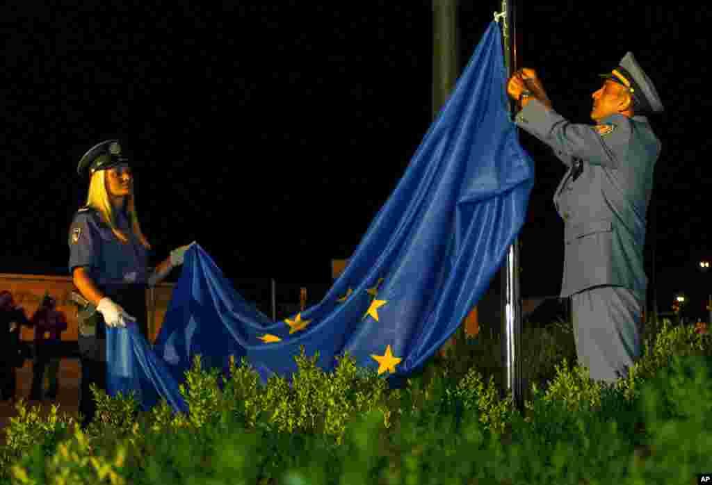 Xorvatiya polisi və kömrük rəsmisi Xorvatiya və Sloveniya arasında sərhəddə Avropa İttifaqının bayrağını yüksəldir.