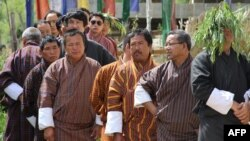 In this photograph taken on July 13, 2013, Bhutanese men wait in line to cast their votes at a polling station in Thimphu.