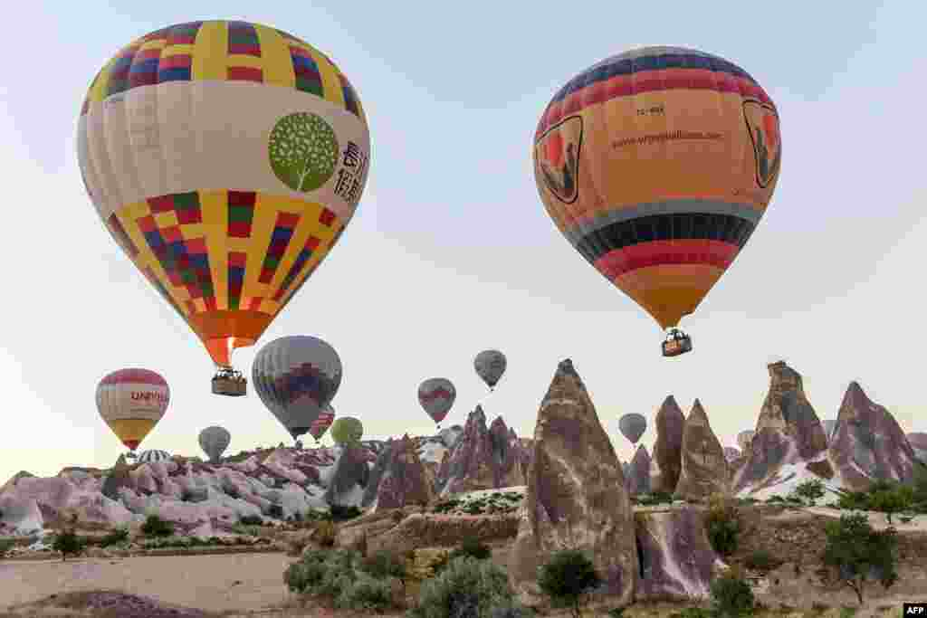 Hot air balloons glide during a flight over Nevsehir in Turkey's historical Cappadocia region, Central Anatolia, eastern Turkey.