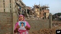 26일 방글라데시 건물 붕괴 사고 현장에서 실종된 딸의 사진을 들고 울고 있는 여성.