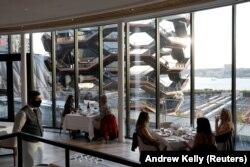 Orang-orang duduk di restoran seafood Mediterania Estiatorio Milos di Hudson Yards ketika restoran mulai membuka kembali layanan makan di dalam ruangan dengan kapasitas 25 persen di Manhattan, New York City, AS, 30 September 2020. (Foto: REUTERS/Andrew Ke