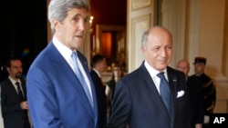 U.S. Secretary of State John Kerry, left, is greeted by France's Foreign Minister, Laurent Fabius, in Paris, July 26, 2014.