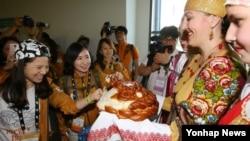14일 오후 러시아 블라디보스토크 국제공항에서 열린 유라시아 친선특급 대표단 환영행사에서 단원들이 러시아 전통 빵을 맛보고 있다.
