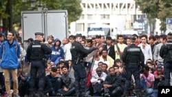 Para migran menunggu dievakuasi dari sebuah kmp di utara Paris (16/9). (AP/Thibault Camus)