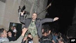 ພວກປະທ້ວງລະບອບການປົກຄອງຂອງຊີເຣຍ ແບກຫາມທະຫານ ຊິເຣຍທີ່ໂຕນໜີ ພາກັນຮ້ອງໂຮປະນາມ ປະທານາທິບໍດີຊິເຣຍ ທ່ານ Bashar Assad ທີ່ເມືອງ Rastan ໃນແຂວງ Homs, ພາກກາງຂອງຊິເຣຍ, ໃນວັນຈັນເດືອນມັງກອນທີ 30, 2012.