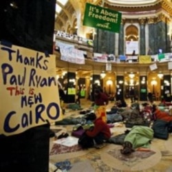 "Protesters sleep in the Wisconsin state Capitol in Madison on Thursday at the start of the 10th day of protests. A sign refers to ""New Cairo"" after Paul Ryan, a Republican congressman, compared the protests to the recent events in Cairo."