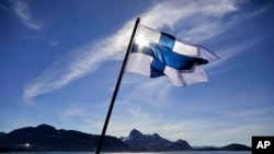 FILE - In this Saturday, July 29, 2017 file photo, Finland's flag flies aboard the Finnish icebreaker MSV Nordica as it arrives into Nuuk, Greenland. Finland has come out on top of an international index that measures nations by how happy they are as plac