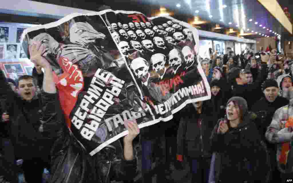 "Opposition demonstrators hold a poster reading ""Give back the elections, rascals"" during protests against alleged vote rigging in Russia's parliamentary elections in Triumphal Square in Moscow, Russia, Tuesday, Dec. 6, 2011. Police clashed Tuesday on a c"