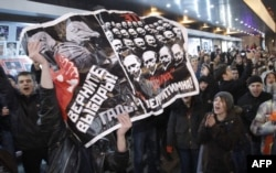 "FILE - Opposition demonstrators hold a poster reading ""Give back the elections, rascals"" during protests against alleged vote rigging in Russia's parliamentary elections in Triumphal Square in Moscow, Russia, Dec. 6, 2011."
