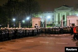 FILE - Riot police form a cordon in front of the Russian embassy during the annual far-right march, which coincides with Poland's national Independence Day, in Warsaw, Nov. 11, 2013.