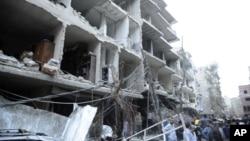 Đám đông tập trung dưới tòa nhà bị phá hủy do xe bom nổ, Damascus, Syria, 26-10-2012.