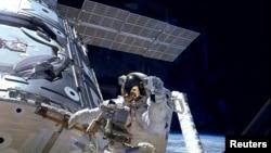 美宇航员在国际空间站外面行走的资料照片。