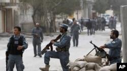 阿富汗警察持槍在遭受塔利班武裝反叛分子襲擊的建築前看守。