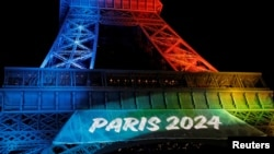 FILE - The Eiffel Tower is lit in the colors of the Olympic flag during the launch of the international campaign for the Paris bid to host the 2024 Olympic Games, in Paris, Feb. 3, 2017.