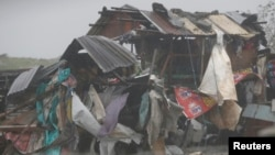 FILE - A squatter's house is pounded as a typhoon hits the coastal town of Bacoor, Cavite southwest of Manila, July 16, 2014.