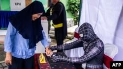 ພະນັກງານປະຕິບັດງານໃນການເລືອກຕັ້ງ ນຸ່ງຊຸດຍອດມະນຸດ Spiderman ຊ່ວຍພວກໄປປ່ອນບັດລົງທະບຽນ ຢູ່ສະຖານທີ່ປ່ອນບັດໃນເມືອງ ຊູຣາບາຢາ, ວັນທີ 17 ເມສາ, 2019